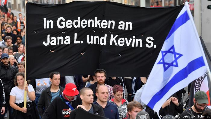 People march in an memorial for victims of the Halle synagogue attack, holding up a banner and an Israeli flag