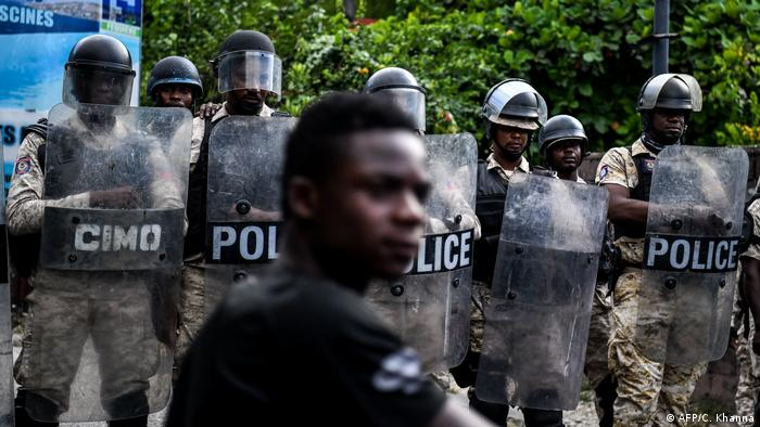 A Haitian protester stands in front of a row of riot police