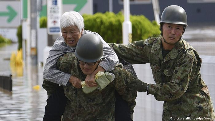 An old lady being carried on the back of a rescuer