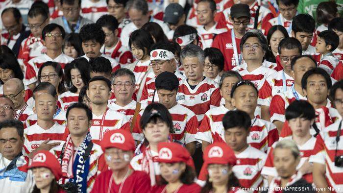 Japanese fans close their eyes at the moment of silence for the typhoon victims (picture-alliance/ZUMAPRESS/R. Reyes Marin)