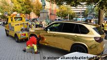 13.10.2019, Nordrhein-Westfalen, Düsseldorf: Ein goldener SUV wird nahe der Königsallee abgeschleppt. Weil der mit goldfarbener Folie überzogene BMW X5 eventuell zu grell für den Straßenverkehr ist, hat die Düsseldorfer Polizei das Fahrzeugam 13.10.2019 vorläufig aus dem Verkehr gezogen. Der Wagen war bei einer Kontrolle gegen Auto-Poser aufgefallen. Foto: Gerhard Berger - ACHTUNG: Personen wurden aus rechtlichen Gründen gepixelt +++ dpa-Bildfunk +++ | Verwendung weltweit