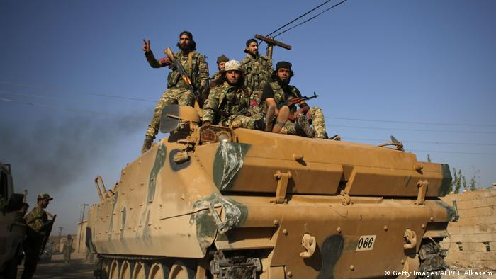 Turkey-backed Syrian fighters on a tank in Tal Abyad, October 13