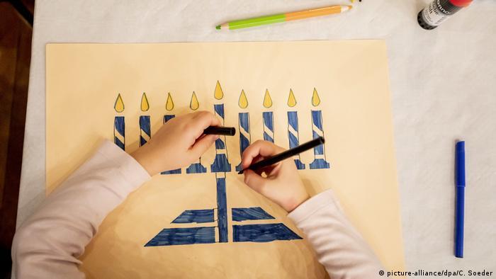 Kids' hands drawing a Hanukkah menorah
