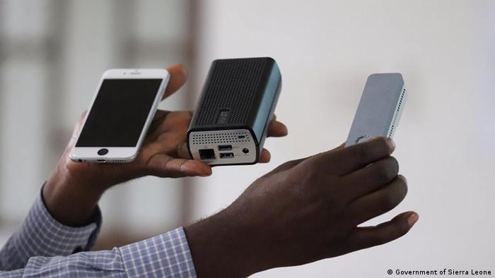 Hands holding three devices – MinION, power bank and a smartphone (Government of Sierra Leone)