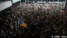 A protester holds a Catalan pro-independence Estelada flag surrounded by other protesters at El Prat airport in Barcelona on October 14, 2019 as thousands took to the streets after Spain's Supreme Court sentenced nine Catalan separatist leaders to between nine and 13 years in jail for sedition over the failed 2017 independence bid. - As the news broke, demonstrators turned out en masse, blocking streets in Barcelona and elsewhere as police braced for what activists said would be a mass response of civil disobedience. (Photo by LLUIS GENE / AFP)