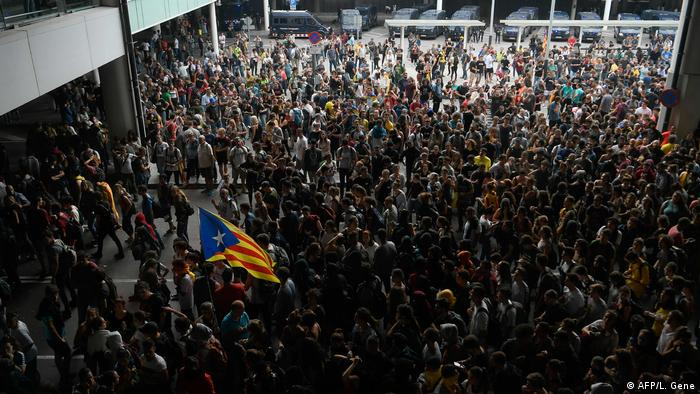A protester holds a Catalan pro-independence Estelada flag surrounded by other protesters at El Prat airport in Barcelona
