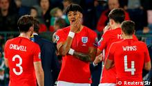 England's Tyrone Mings and teammates stand during a break in play (Reuters/Str)