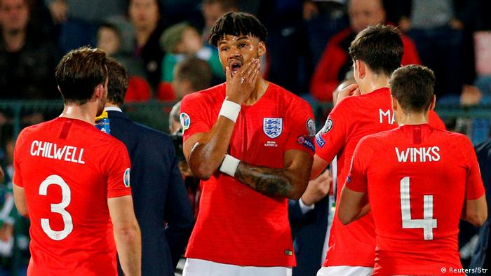 England's Tyrone Mings and teammates stand during a break in play