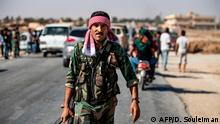 October 14, 2019*** Syrian regime forces are pictured as they patrol a street on the western entrance of the town of Tal Tamr in the countryside of Syria's northeastern Hasakeh province on October 14, 2019. - Syrian regime forces moved towards the Turkish border Monday after Damascus reached a deal with beleaguered Kurdish forces following a US withdrawal announcement, AFP correspondents reported. Soldiers waving Syrian flags deployed west of Tall Tamr, not far from the flashpoint border town of Ras al-Ain, which has been a key target of Turkish forces and their proxies since they launched their onslaught six days ago. (Photo by Delil SOULEIMAN / AFP)