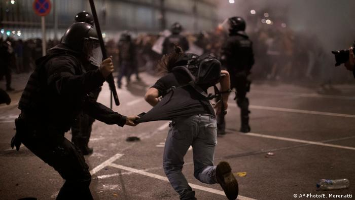 Demonstrators run away from Police officers outside El Prat airport in Barcelona
