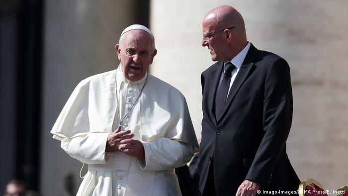 Pope Francis and Domenico Giani talking.