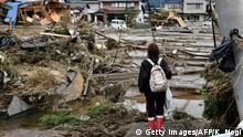 A woman looks at flood-damaged homes in Nagano on October 15, 2019, after Typhoon Hagibis hit Japan on October 12 unleashing high winds, torrential rain and triggered landslides and catastrophic flooding. - Rescuers in Japan worked into a third day on October 15 in an increasingly desperate search for survivors of a powerful typhoon that killed nearly 70 people and caused widespread destruction. (Photo by Kazuhiro NOGI / AFP) (Photo by KAZUHIRO NOGI/AFP via Getty Images)