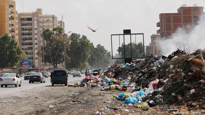 Cars pass next to mounds of rubbish in Tripoli, Libya