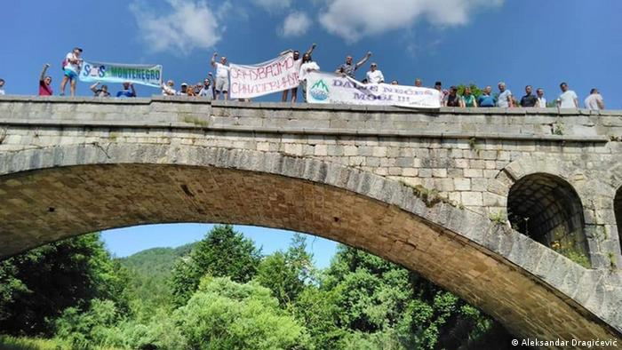 A group of activists pose for a picture as they commandeer one of the bridges crossing the River Bukovica