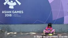 This picture taken on October 4, 2019 shows a girl eating her lunch besides a banner for the 2018 Asian Games in Jakarta. - A diet heavy on cheap, modern food like instant noodles that fills bellies but lacks key nutrients has left millions of children unhealthily thin or overweight in southeast Asia, experts said on October 15. (Photo by GOH CHAI HIN / AFP) (Photo by GOH CHAI HIN/AFP via Getty Images)