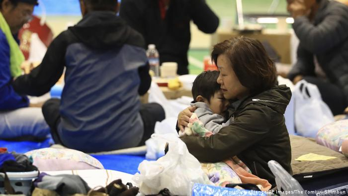 A woman cradles her son in a rescue center in Nagano city