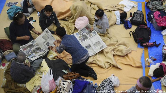 People make beds and read newspapers in an emergency center after the overflow of Chikuma river in Nagano city