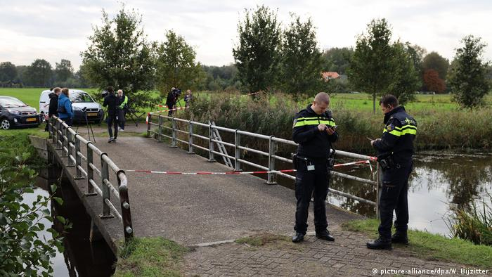 Police stand outside a cordoned off drive to the isolated farm