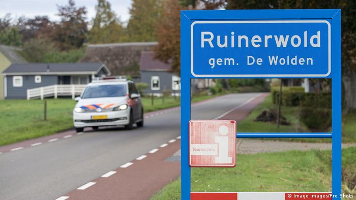 A road sign for Ruinerwold and a police car