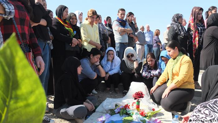 A family at the grave of a Kurdish fighter