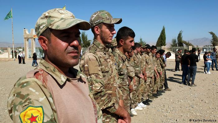 A group of YPG fighters listen to a speech in Derik