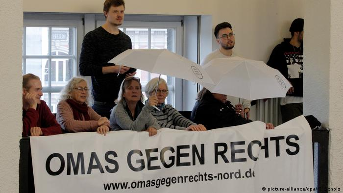 Grandmothers against the right hold umbrellas which say Omas gegen Rechts