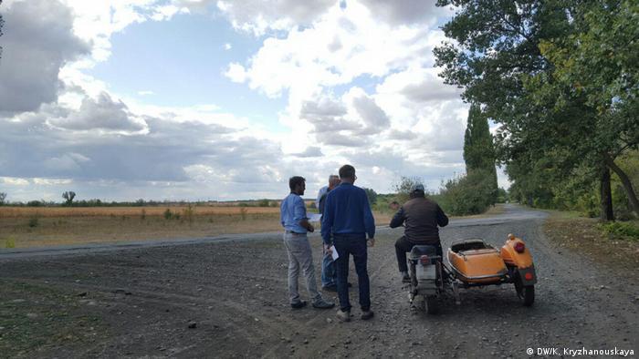 Немцы разговаривают с местным жителем, приехавшим на мотоцикле