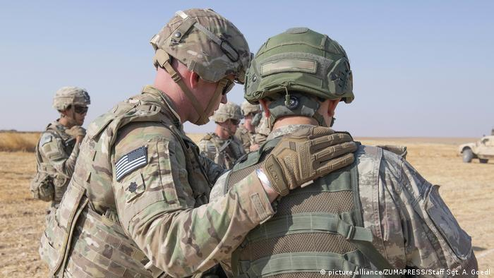 A US troop pats another troop on the back (picture-alliance/ZUMAPRESS/Staff Sgt. A. Goedl)