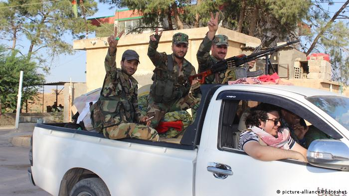 Syrian troops sit in the back of a truck after entering the town of Tall Tamr (picture-alliance/Photoshot)