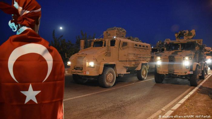A Turkish convoy drives down the street at night while a person wrapped in a Turkish flag watches the convoy (picture-alliance/AA/M. Akif Parlak)