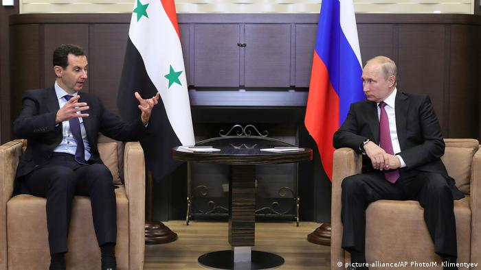 Vladimir Putin and Bashar Assad sit in two chairs in front of their respective flags (picture-alliance/AP Photo/M. Klimentyev)