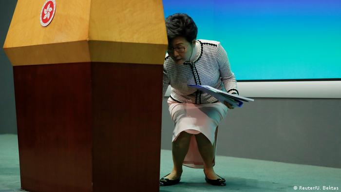 Carrie Lam picks up her notes from the floor