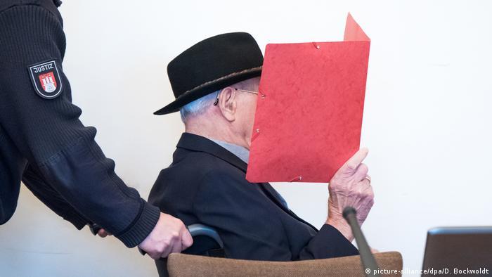 Подсудимого везут в инвалидном кресле в зал заседаний. Он закрывает лицо от фотографов