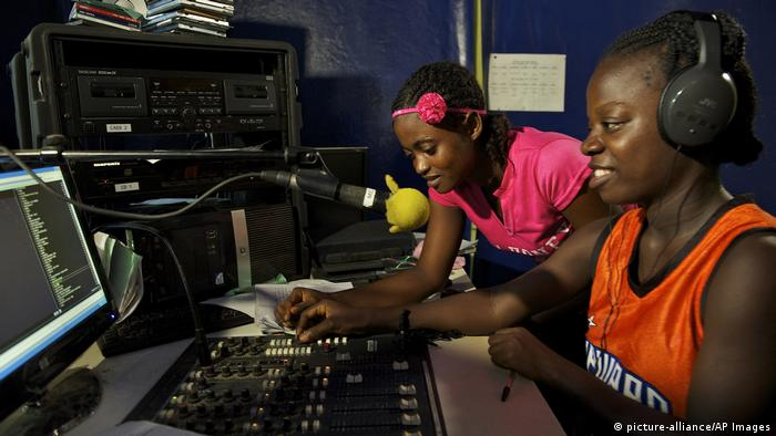 Two young women broadcast from a radio panel in Liberia