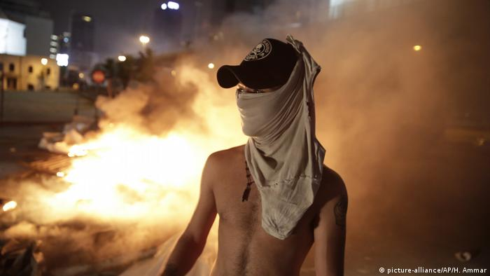 Protester in front of flame wearing a protective cloth around his face
