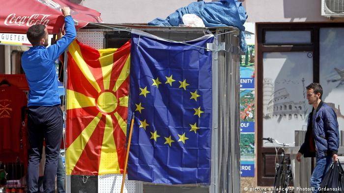 A street vendor fixes a North Macedonia flag next to an EU flag in a street in Skopje, North Macedonia