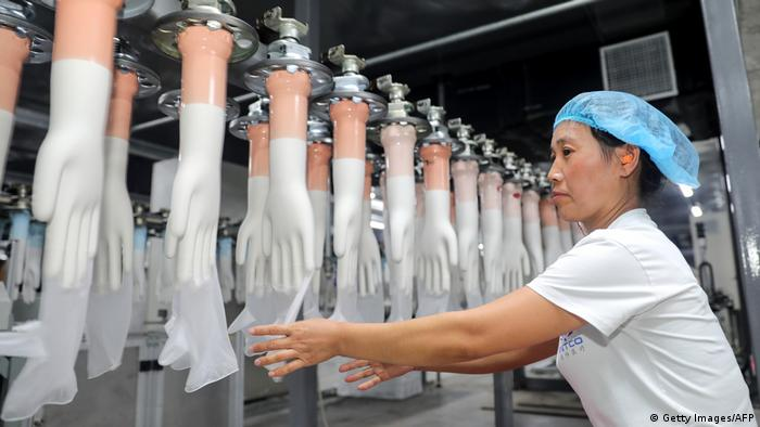 This photo taken on August 14, 2019 shows an employee working on a medical glove production line at a factory in Huaibei in China's eastern Anhui province