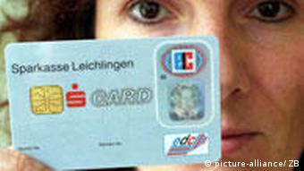 A woman holds up a microchip debit card.