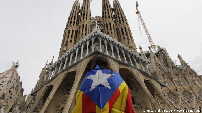 A protester stands in front of the Sagrada Familia