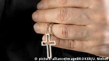 Hand hält eine Kette mit Kreuzanhänger | Verwendung weltweit, Keine Weitergabe an Wiederverkäufer.