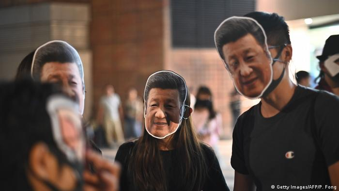 Protesters clad in masks showing the face of Chinese President Xi Jinping gather for a human chain rally in Hong Kong's Sha Tin district on October 18, 2019.
