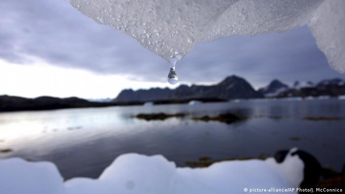 A water droplet drops from a piece of ice