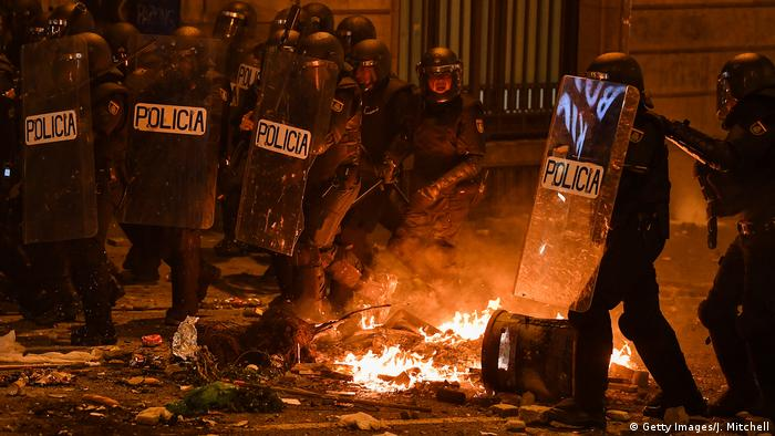 Police officers stand in front of a fire as protesters called a general strike following a week of protests