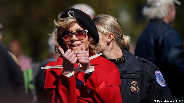Jane Fonda mit Handschellen und erhobenen Daumen, hinter ihr eine Polizistin