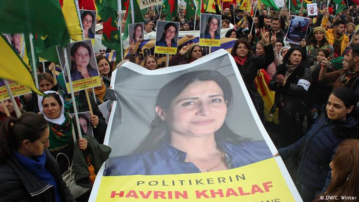 Women hold a portrait of Havrin Khalaf at a protest in Cologne (DW/C. Winter)