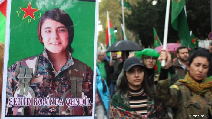 A Kurdish woman holds a placard of Martyr Rojinda Qendil at a protest in Cologne (DW/C. Winter)