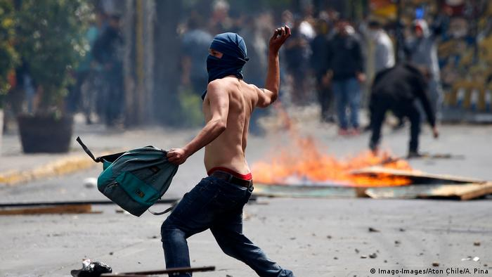 A protester hurls a rock in the street of Santiago