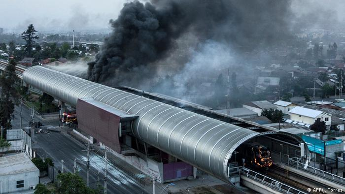 A large cloud of smoke rises from a metro station