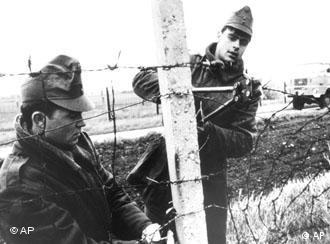 Soldados húngaros desmontam as cercas de arame farpado