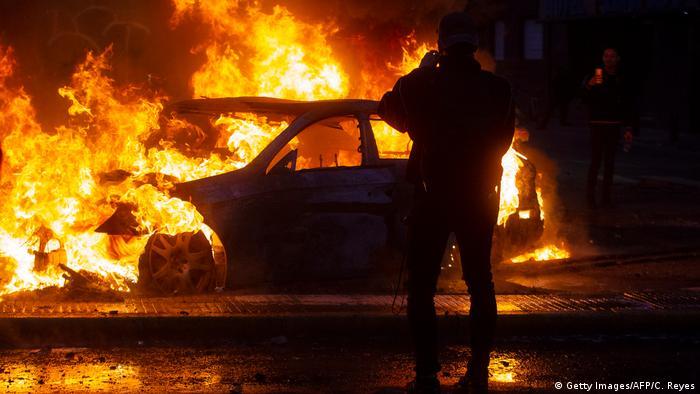 A burning car on a street in Santiago
